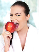 Young Woman in White Bathrobe Biting an Apple — Stok fotoğraf