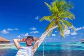 Gorgeous Man Resting on Beach Palm Tree — Stock Photo