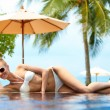 Постер, плакат: Blond woman sunbathing near pool