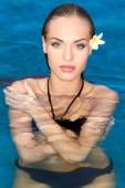 Exotic woman with frangipani in hair — Stock Photo