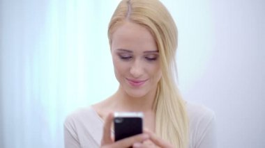 Pretty blond woman texting on her mobile — Stock Video