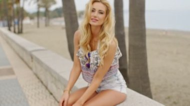 Blond Woman Sitting on Stone Wall at Beach — Stock Video