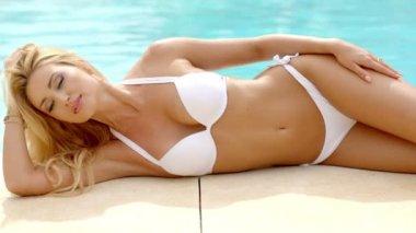 Blond Woman in White Bikini Lying Next to Pool — Stock Video