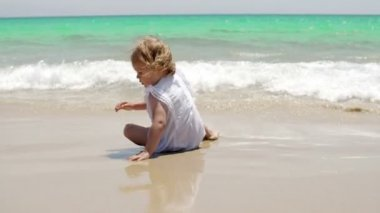 Little girl romping at the edge of the surf — Stock Video