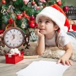 Dreaming little girl in Santa hat writes letter to Santa Claus — Stock Photo #55317169