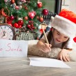 Pretty little girl in Santa hat writes letter to Santa — Stock Photo #55317173