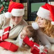 Girl with parents looking gifts nearthe christmas tree — Stock Photo #55317177