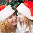 Happy mother and daughter in santa hats — Stock Photo #55317187