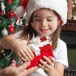 Happy little girl in Santa hat opens red gift box for Christmas — Stock Photo #55317205