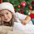 Happy little girl with letter to Santa near christmas tree — Stock Photo #55317209