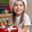 Happy little girl in Santa hat holding red gift box — Stock Photo #55317211