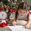 Pretty little girl in Santa hat writes letter to Santa — Stock Photo #55317219