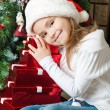 Happy girl in Santa hat with gifts near christmas tree — Stock Photo #55317873