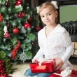Girl in white jacket with gifts near christmas tree — Stock Photo #55317917
