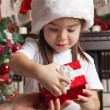 Little girl in Santa hat opens red gift box for Christmas in fat — Stok fotoğraf #55317919