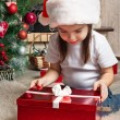Little girl in Santa hat opens red gift box for Christmas — Stok fotoğraf #55318315