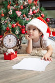 Dreaming little girl in Santa hat writes letter to Santa Claus — Stock Photo