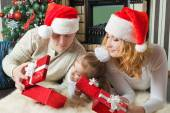 Girl with parents looking gifts nearthe christmas tree — Stock Photo