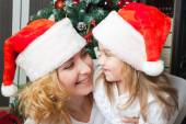 Happy mother and daughter in santa hats — Stock Photo