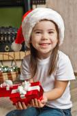 Happy little girl in Santa hat holding red gift box — Stock Photo