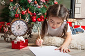 Pretty little girl in Santa hat writes letter to Santa — Stock Photo