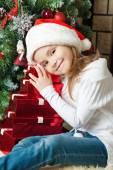 快乐的女孩,在附近的圣诞树礼物的圣诞老人帽子 — 图库照片