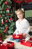 Girl in white jacket with gifts near christmas tree — Foto de Stock