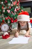 Little girl in Santa hat writes letter to Santa — Stock Photo