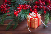 Christmas gift box with decorations on old wooden background — Stock Photo