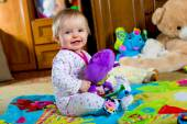 Baby on the carpet with toys — Stock Photo
