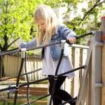 Little girl on outdoor playground equipment — Stock Photo #73828477