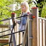 Little girl on outdoor playground equipment — Stock Photo #73828479