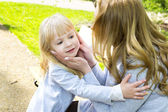 Mother and daughter with flowers playing in spring park. — Stock Photo