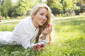 A beautiful young girl with strawberries outdoor — Stock Photo