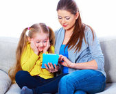 Mother with daughter sitting on sofa home work learning. — Stockfoto