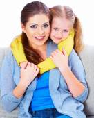 Mother with daughter sitting on sofa with embrace — Stock Photo