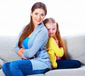 Mother with daughter seat on sofa back to back. — Stockfoto