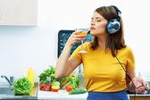 Chica beber jugo en cocina — Foto de Stock