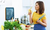 Woman eat in kitchen in cooking time. — Stock Photo