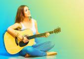 Woman musician with guitar sitting on a floor. — Stock Photo