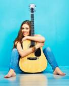 Girl with acoustic guitar sitting on a floor — ストック写真