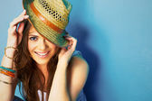 Woman with toothy smile touching hat — Stock Photo