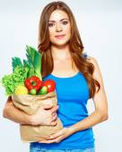 Woman with green vegan food in paper bag. — Stock Photo