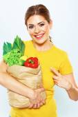 Woman with green food points by finger — Stock Photo