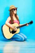 Teenager girl guitar play sitting on a floor. — Stock Photo