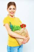 Woman holding paper bag with vegetables — Stock Photo