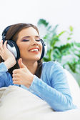 Girl with headphones and thumb up — Stockfoto