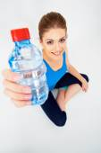 Woman in yoga pose with bottle of water — Stockfoto