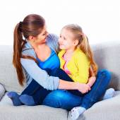 Mother with daughter sitting on sofa — Stock Photo