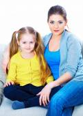 Mom with daughter sitting on sofa — Stock Photo